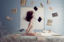 A woman sitting on a bed and flipping her hair back and forth. She has thrown 11 books up in the air and they surround her, falling back onto the bed she is sitting on
